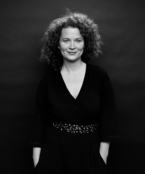 Studio portrait of curly haired woman standing in front of black paper background lit with two Profoto Compact lights